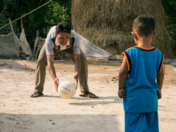 A Children in Families foster father throws a ball to his young son in Cambodia