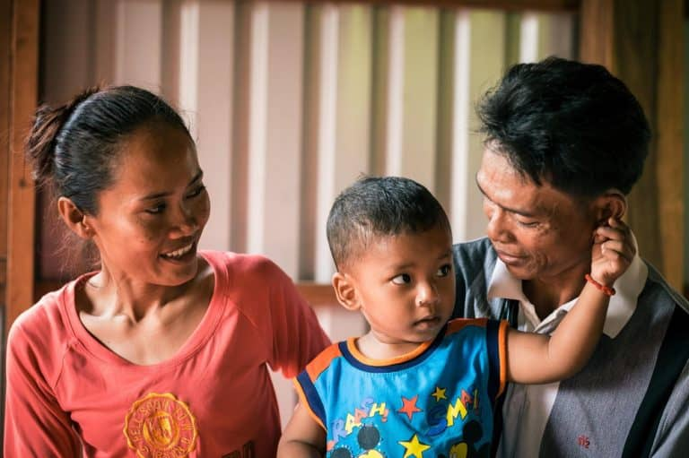 A young Cambodian child sits nestled between his two foster parents