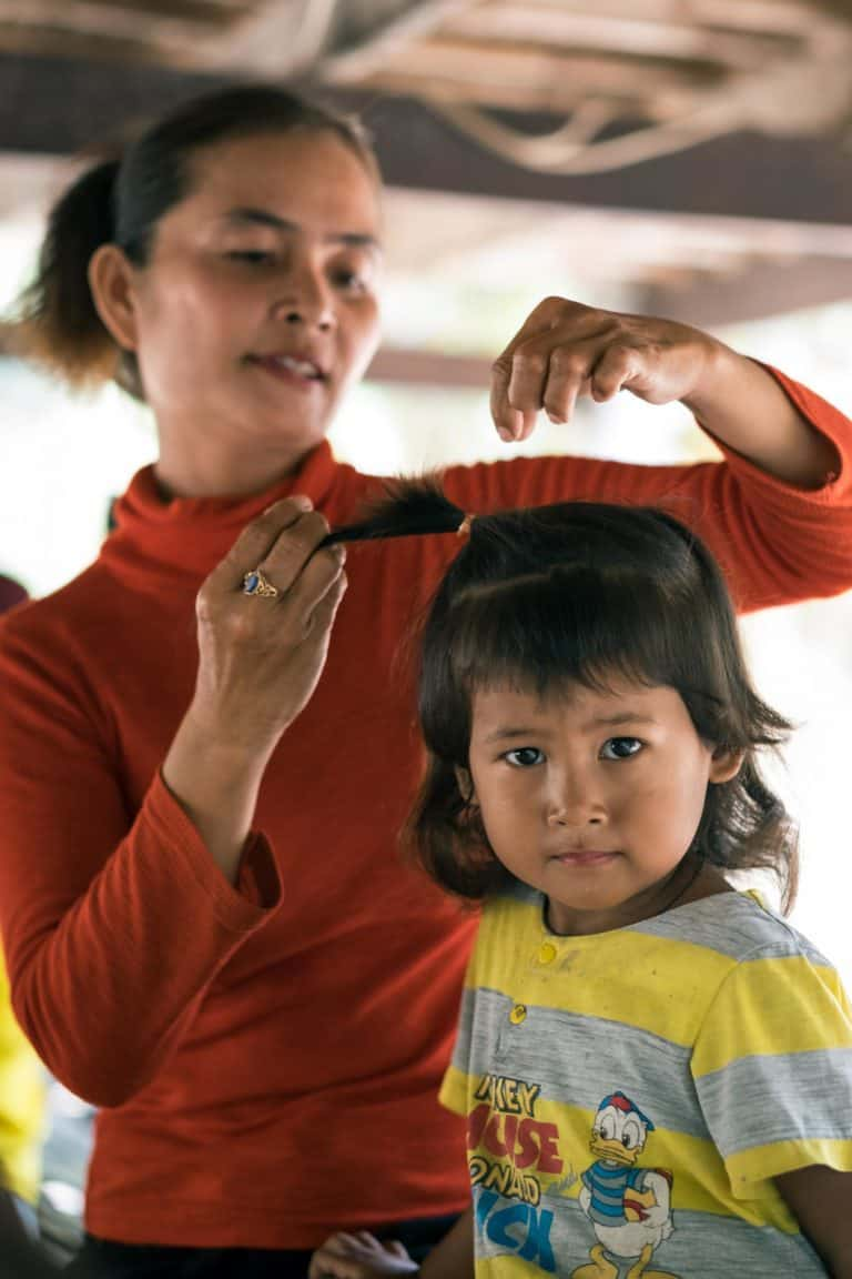 A Children in families foster mum brushes her daughters hair