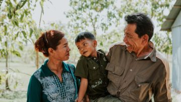 A mother and father look lovingly at their foster child in Cambodia