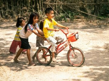 Three foster children from Children in Families push another ABLE child on a bike