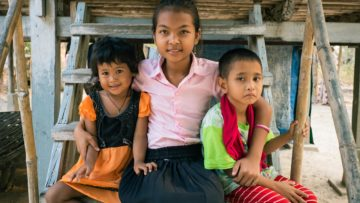 three siblings from Children in Families's ABLE and foster programs sit together on a step
