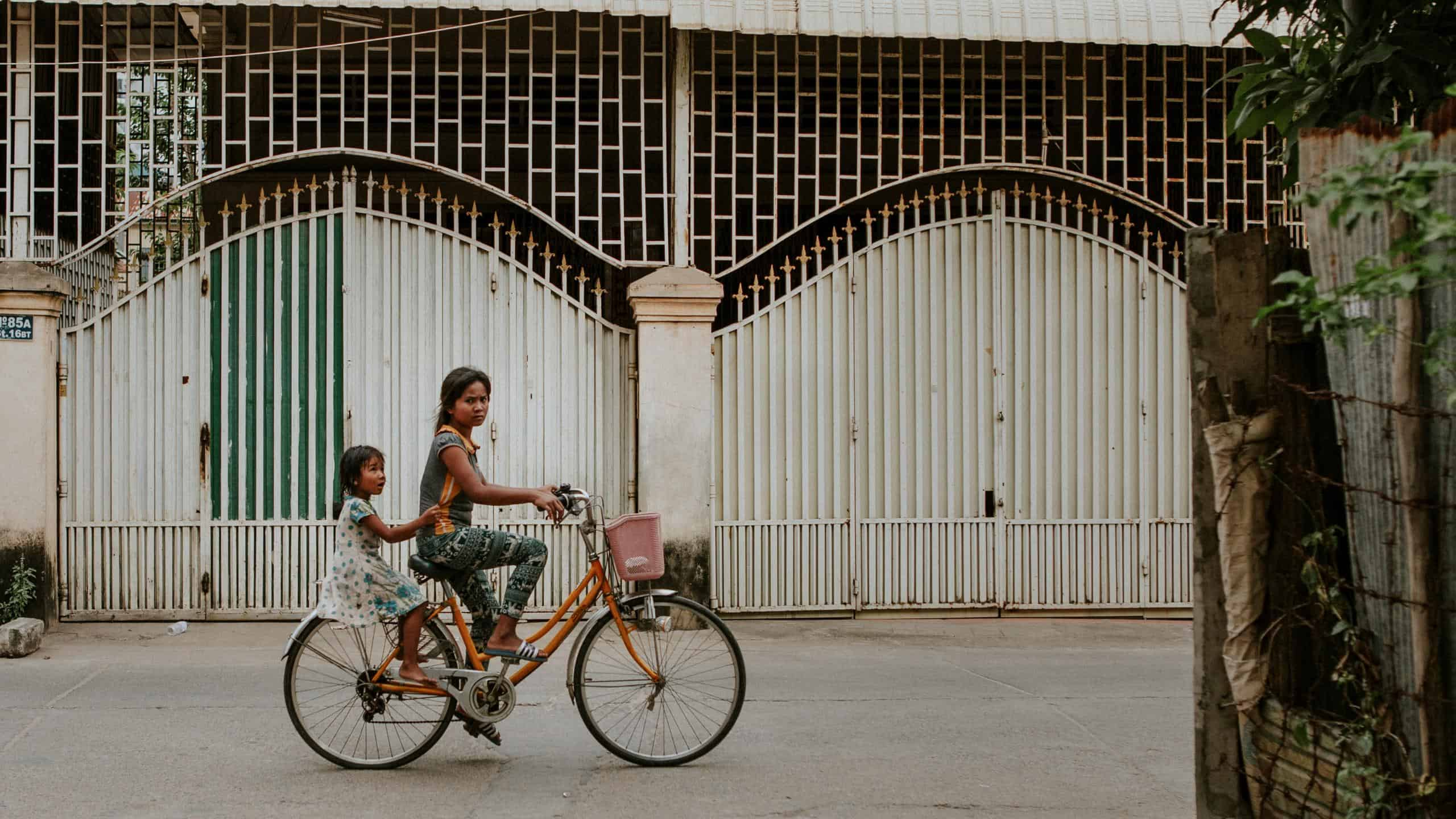 two cambodian girls on a bicycle together in Phnom Penh Cambodia